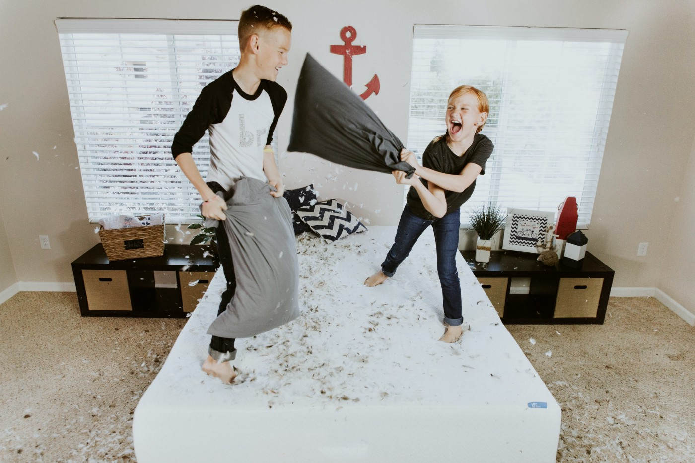 A boy and a girl having a pillow fight