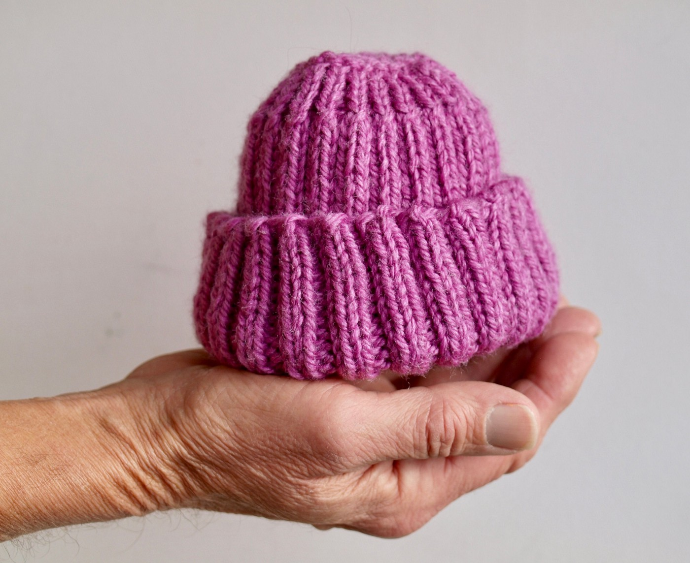 Man holding a woolen cap for babies, don't ask someone when they are having a baby