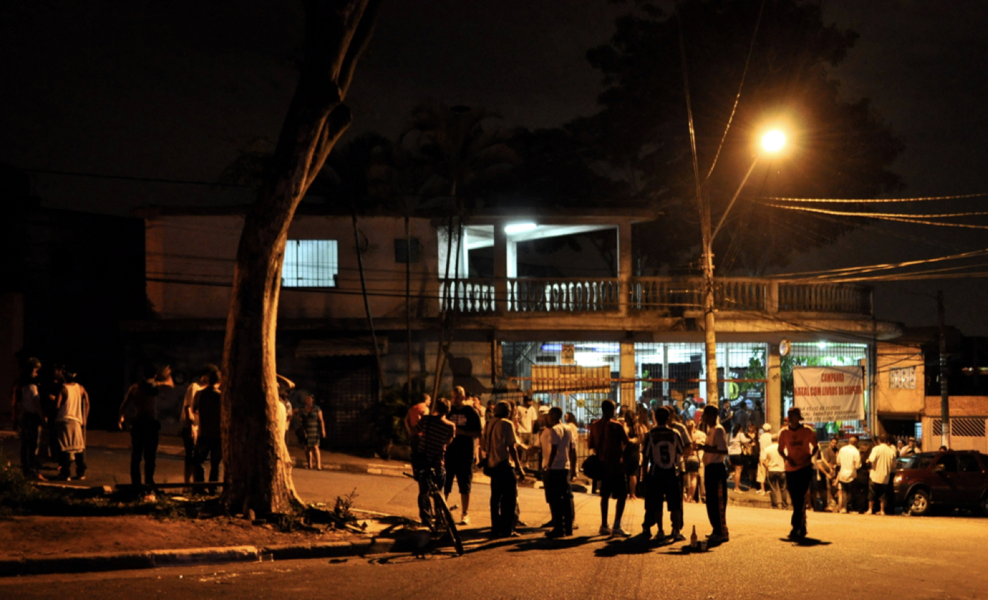 Groups of people spill out of a corner bar into the street at night. They are illuminated by a single street light.