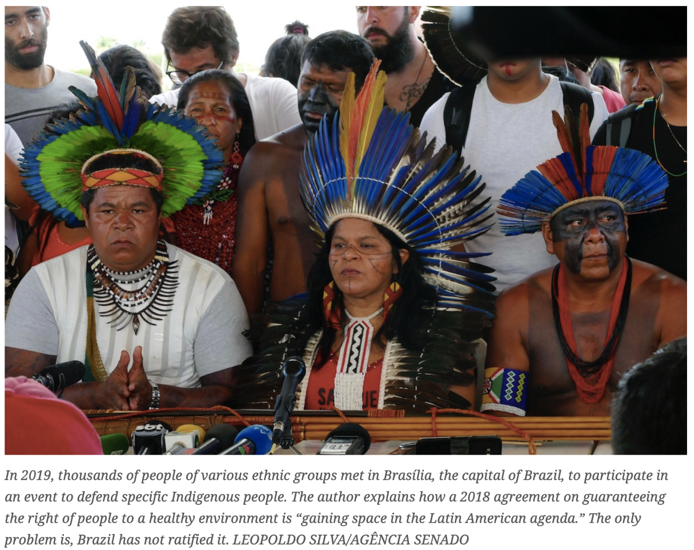 An image 3 people in traditional dress who took part in a 2019 meeting of indigenous people which drew thousands, in Brazil.