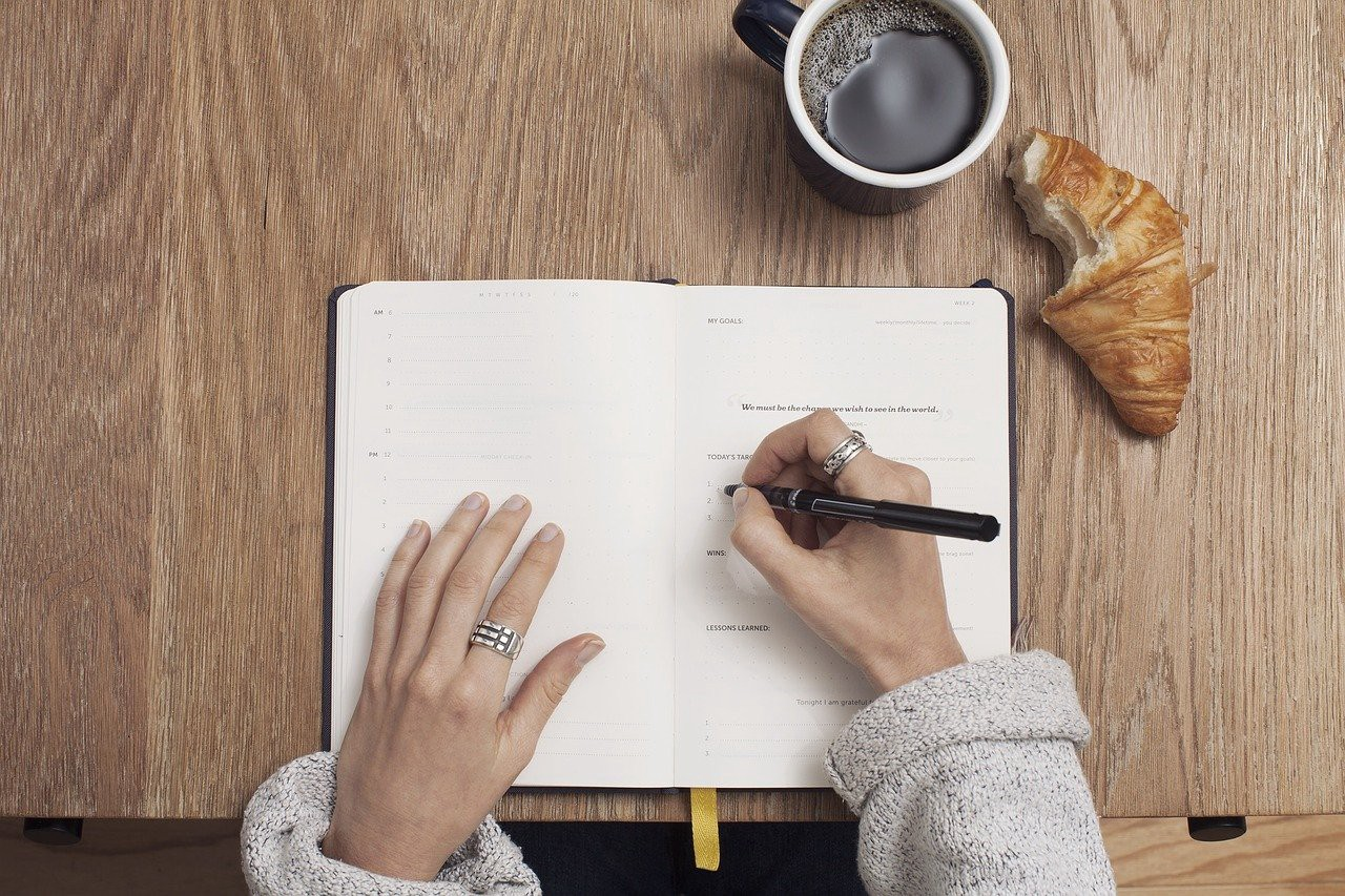 A woman writing in a notebook wearing silver rings. There is a croissant and a cup of coffee next to her.