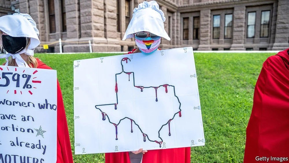 Photo of woman with handmaid's dress holding picture of Texas