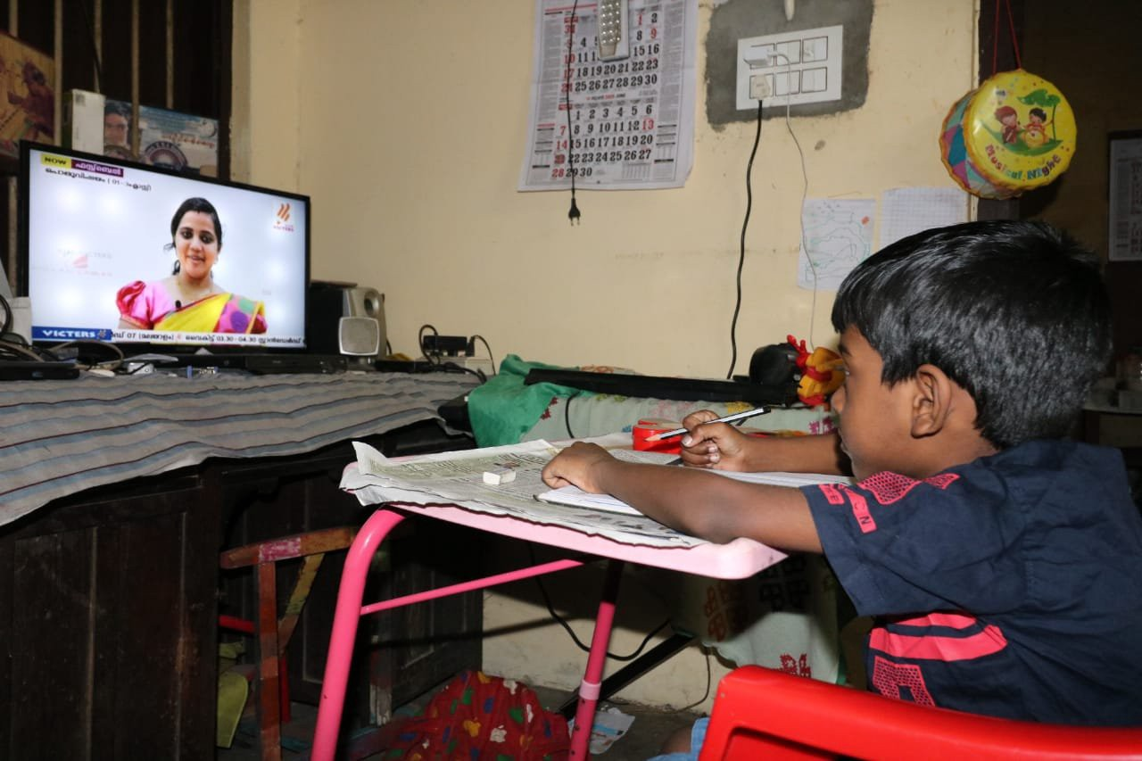 A kid looks at the TV playing a video lesson on the KITE VICTERS channel