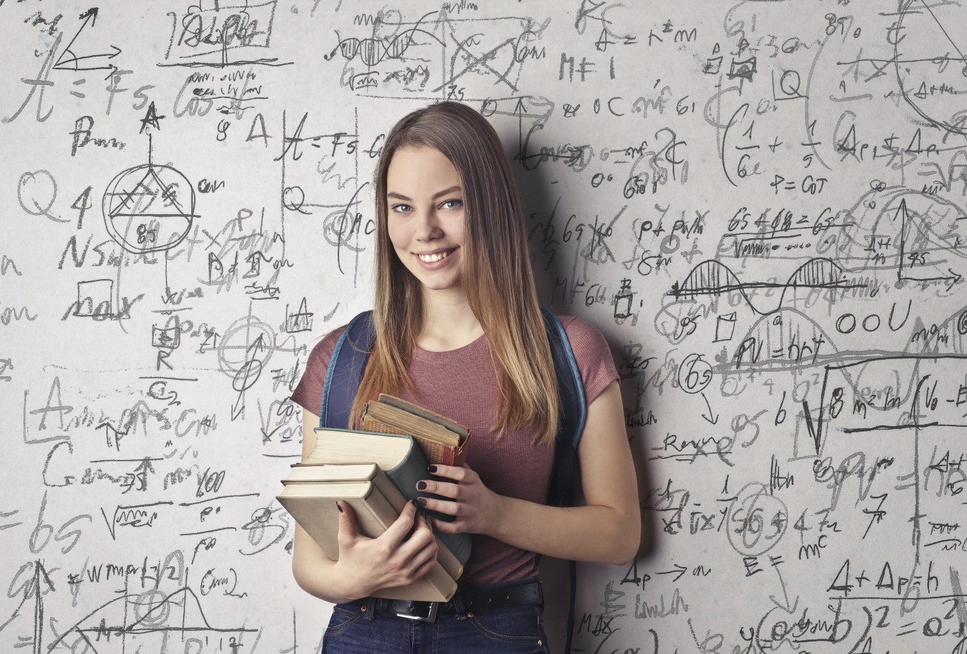 a young girl holds books with a math background behind her