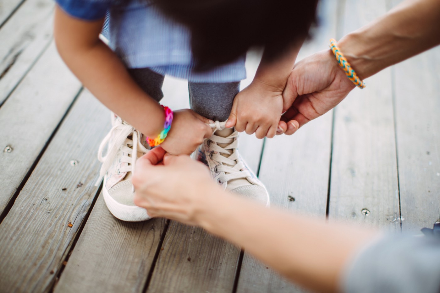 A parent helps a child tie their shoelaces.