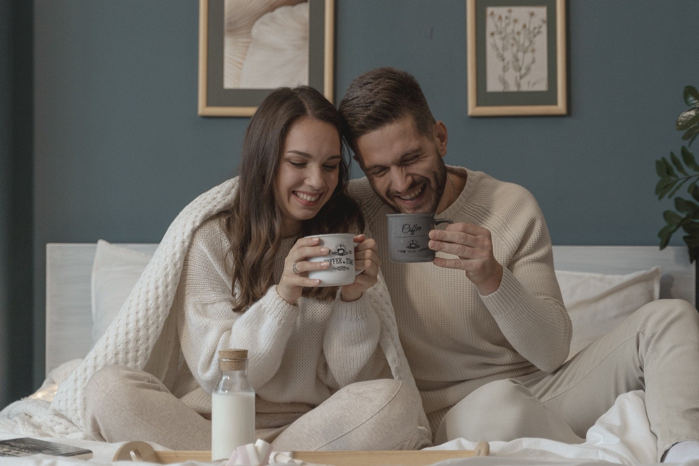 A couple under a blanket drinking out of their mugs