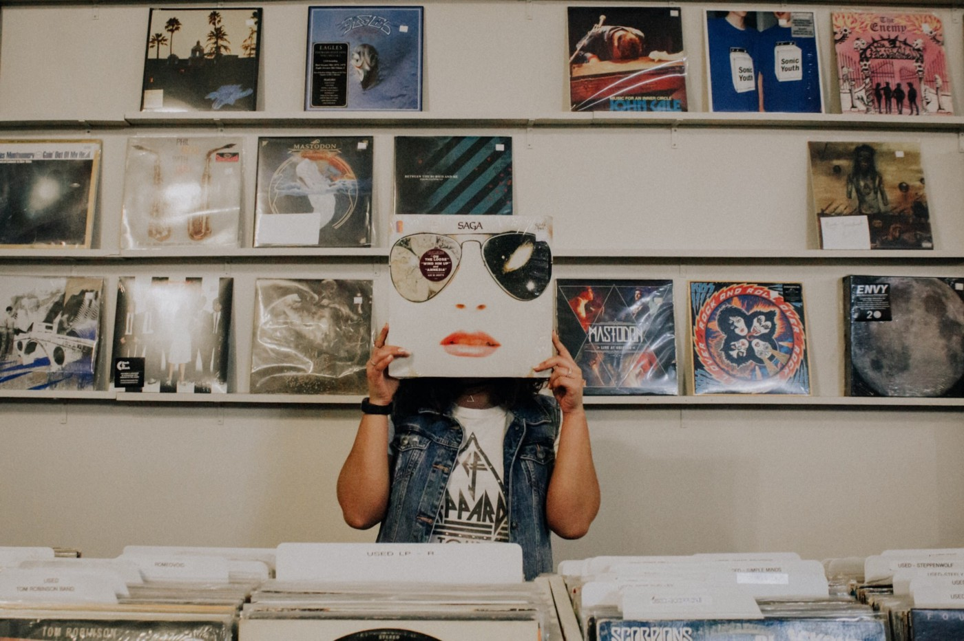person in record store covering their face with a vinyl album cover that has an image of a face on it