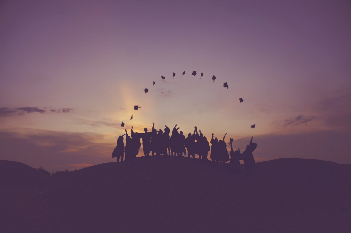 Silhouette of graduates throwing their hats in the air. | Photo by Baim Hanif on Unsplash