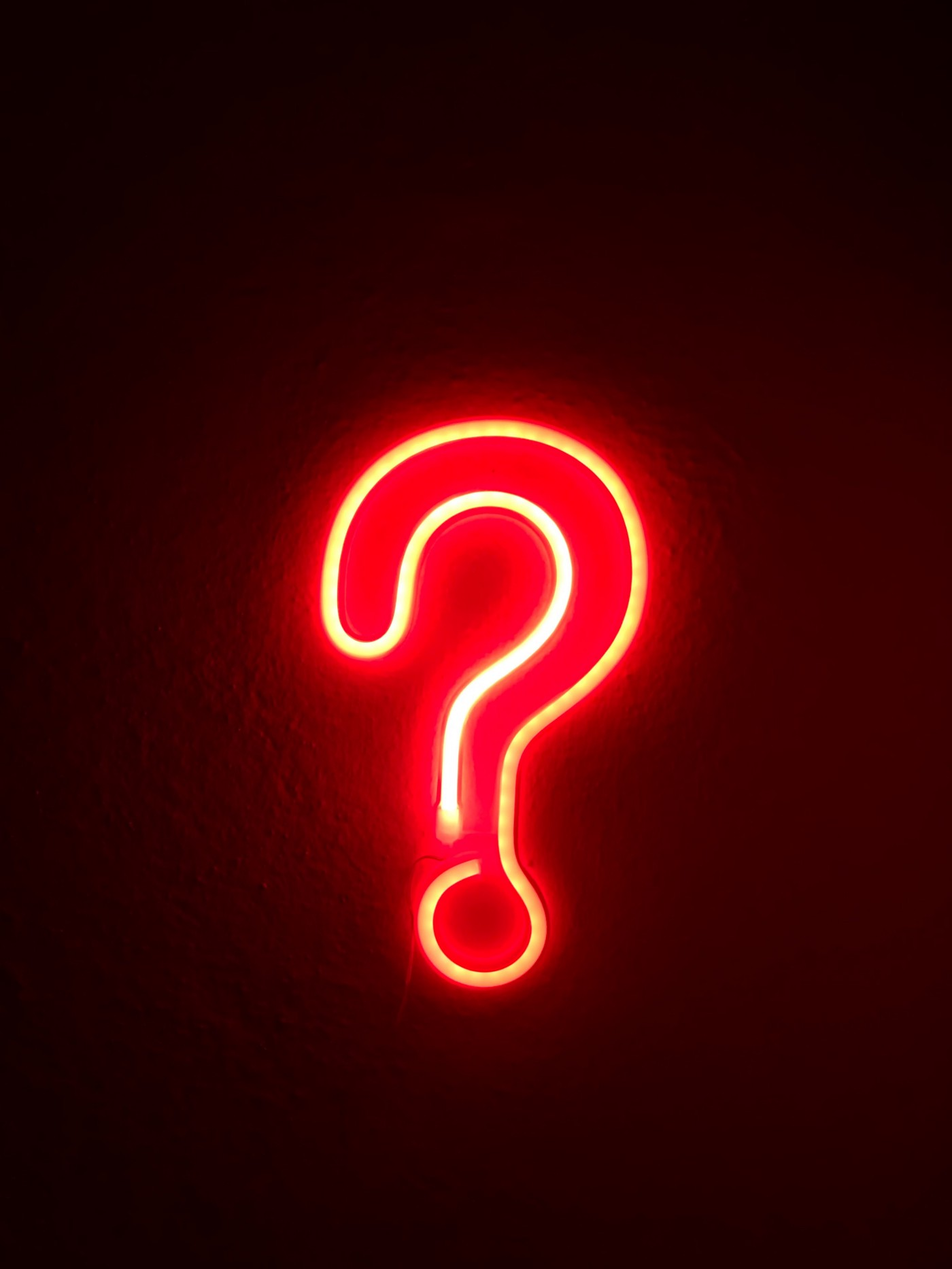 Neon question mark sign on black background
