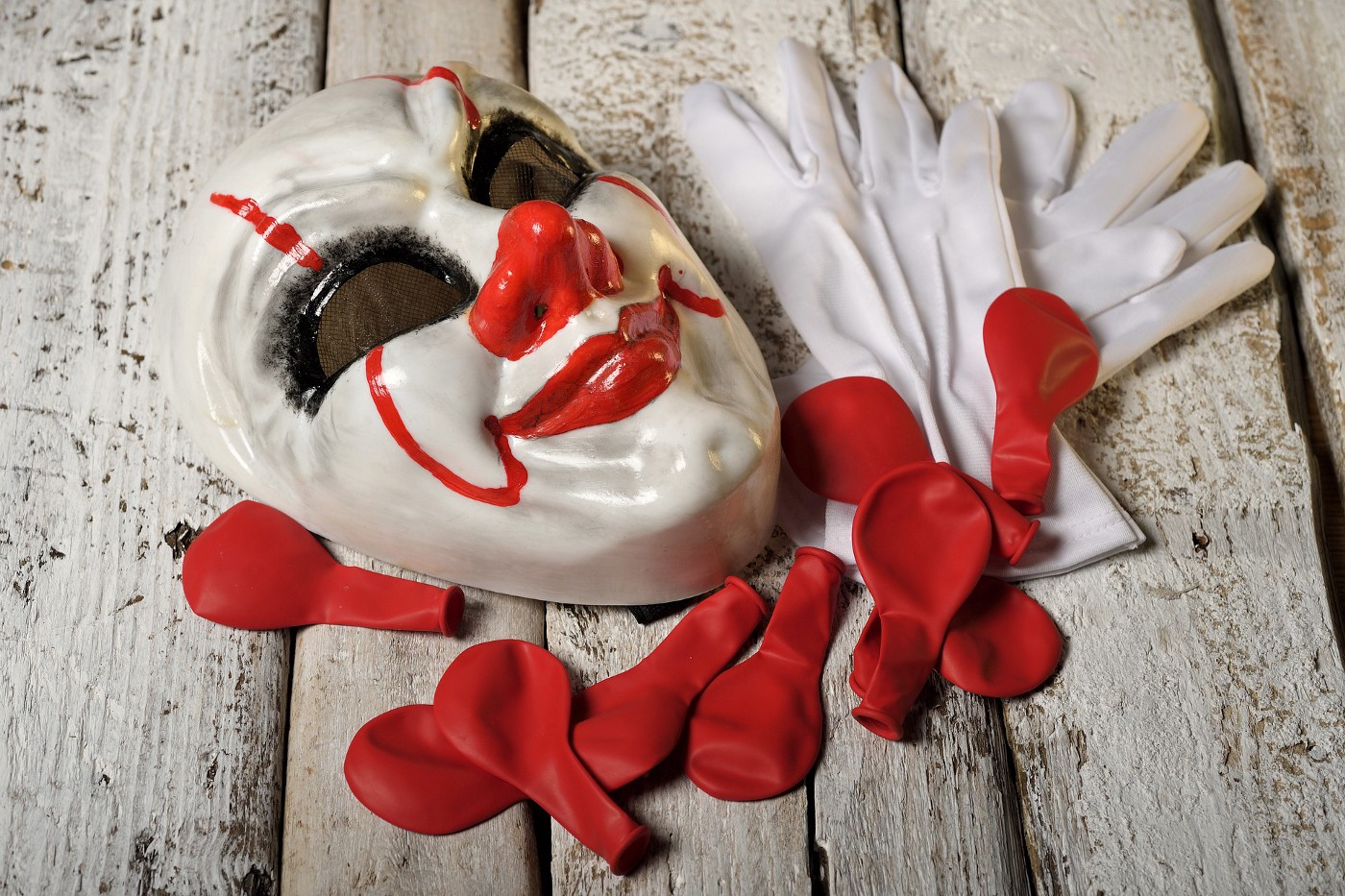 Clowns mask with white gloves and red balloons on wooden boards