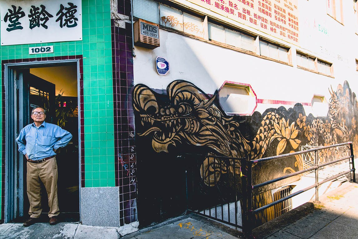 A photo of an Asian man standing in front of a store in Oakland Chinatown. There is a long golden and black dragon mural to the right of him. He is standing in front of a green wall, below a sign written in Chinese.