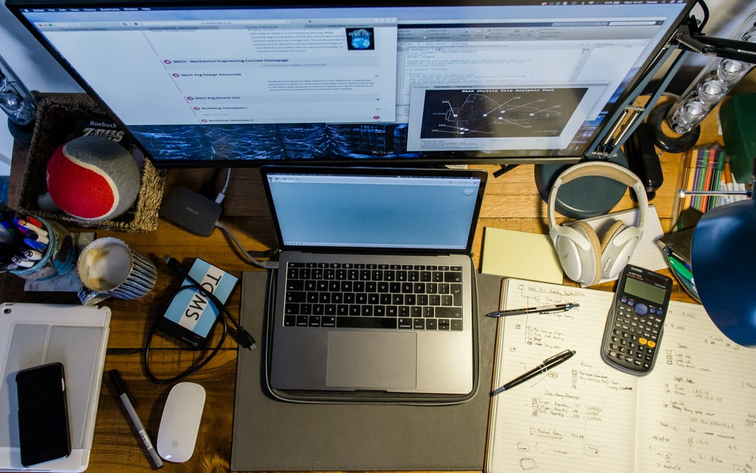 A cluttered desk with headphones, a laptop, a calculator, and other things. The photo is taken from a high angle.