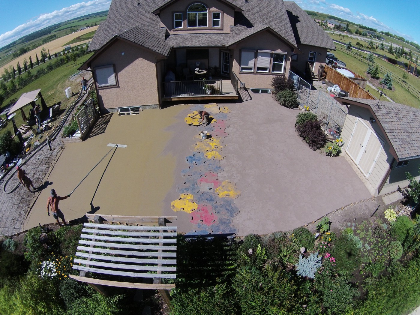 Stamped concrete patio being finished in Calgary. Workers are in the middle of placing fresh concrete and stamping a pattern in it while it's still wet.