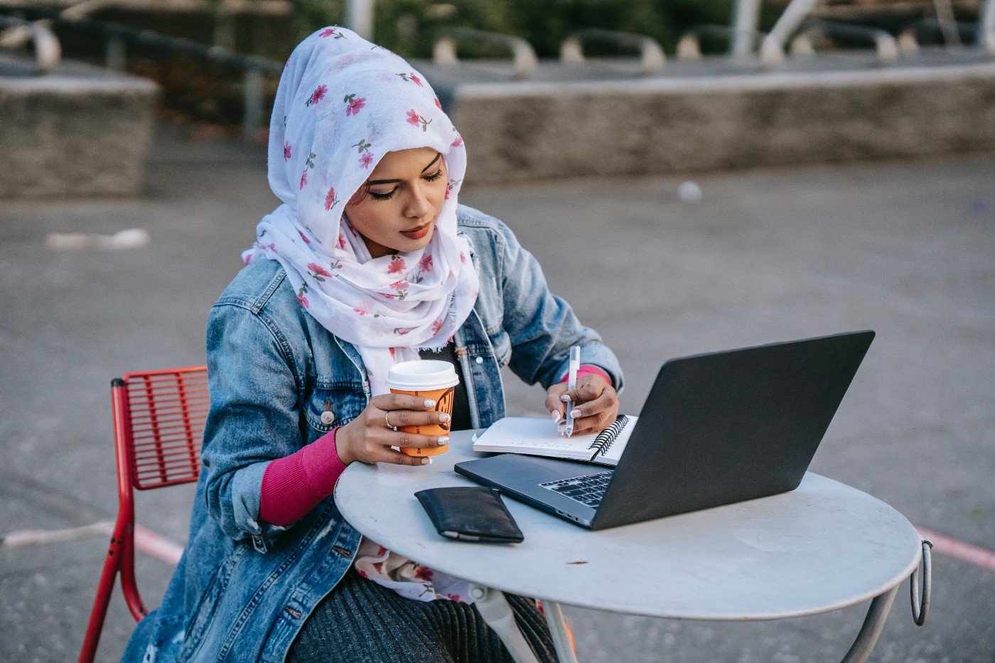 Muslim woman sitting at a table outside. She is working on her laptop while holding a coffee and a pen.