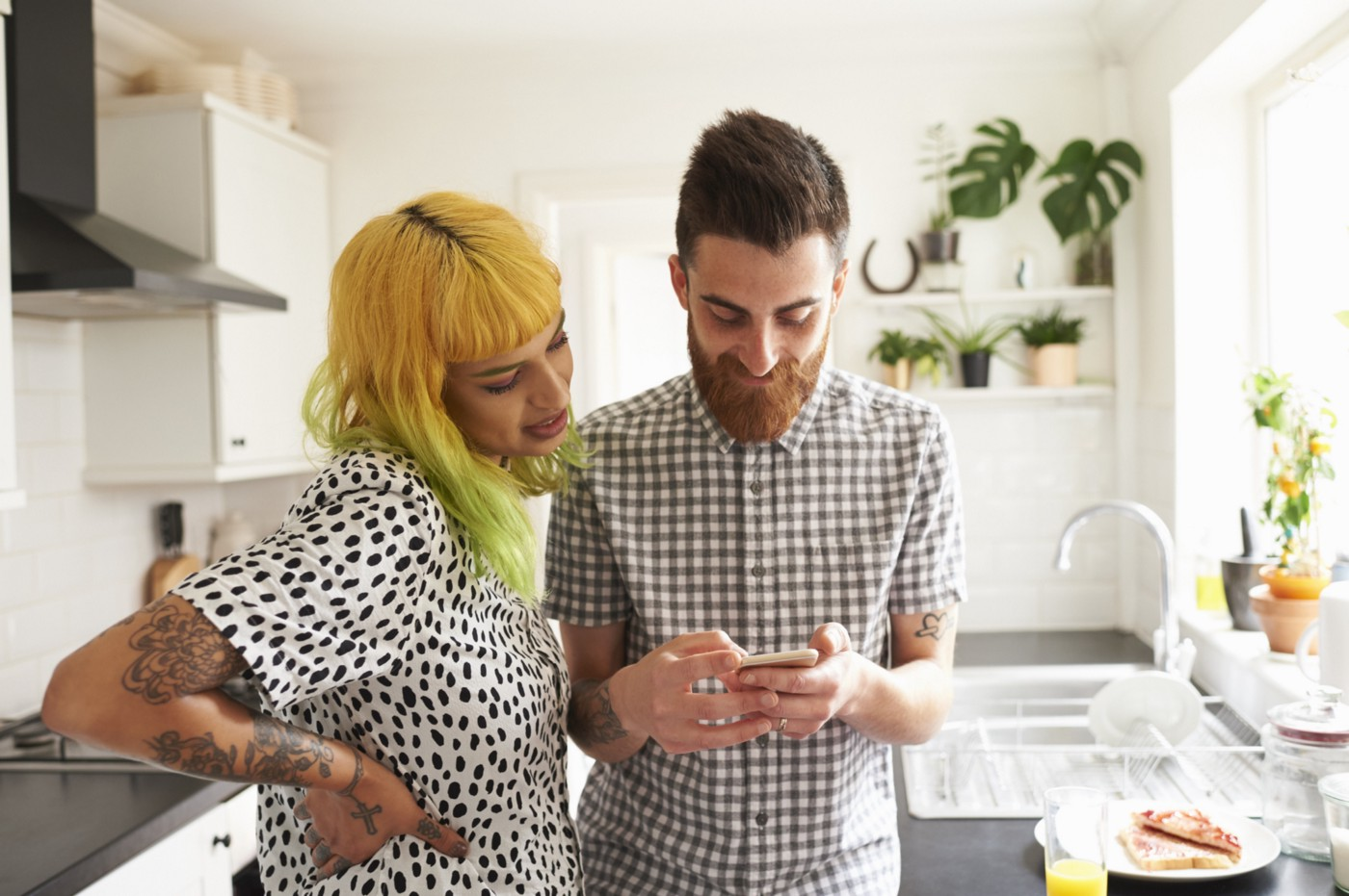 A couple in their kitchen looking at one of their phones.