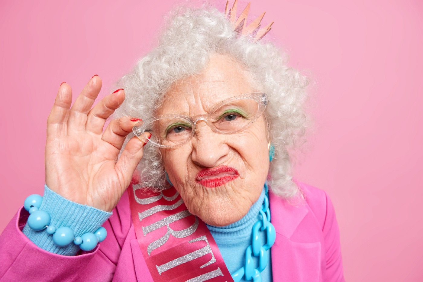 portrait-grey-haired-wrinkled-woman-pouts-lips-looks-attentively-keeps-hand-rim-glasses-dressed-fashionable-clothes—Un Swede