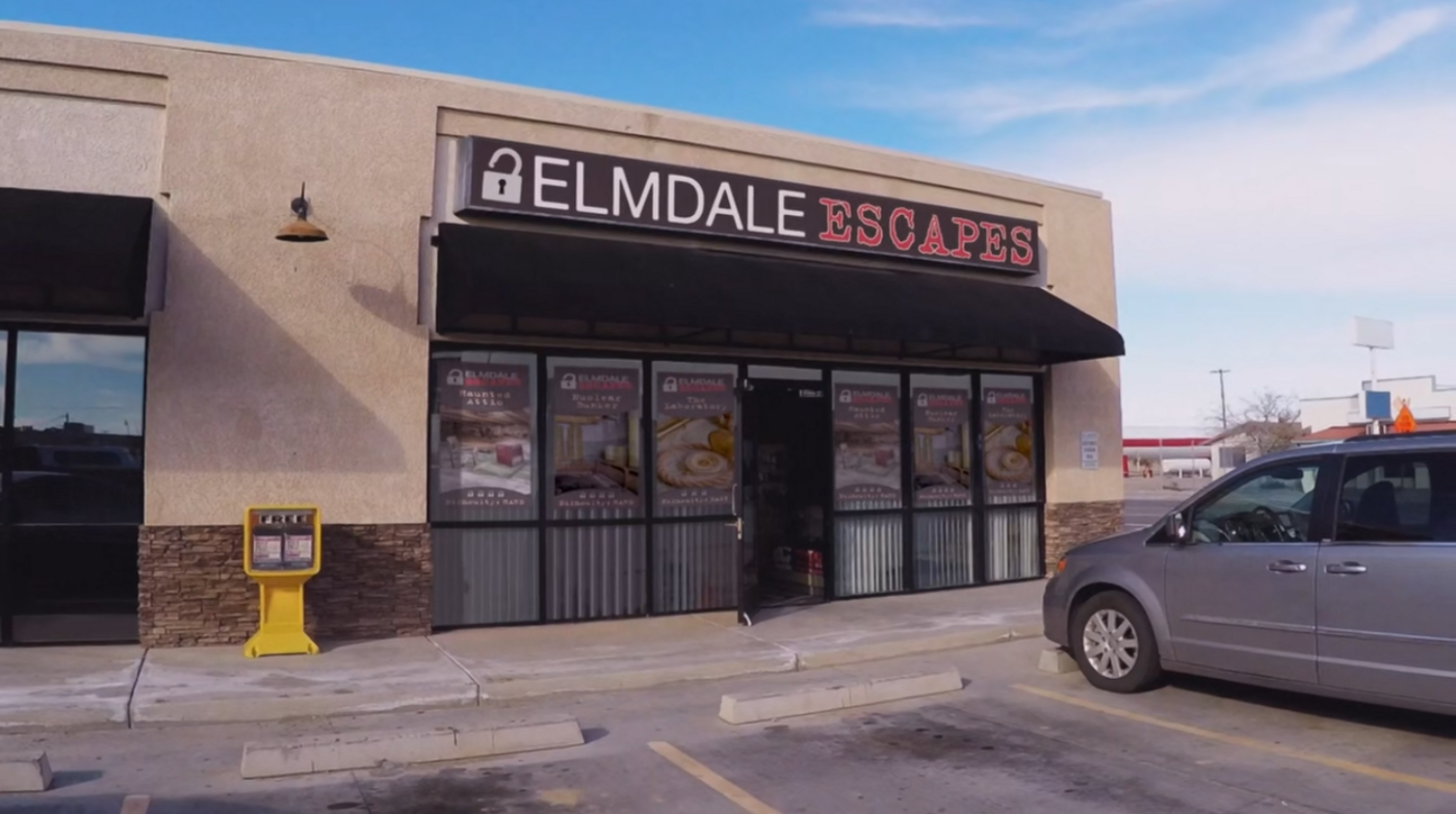 """The exterior of a strip mall shopping area. It's labeled """"Elmdale escapes"""" and has posters in the window advertising games"""