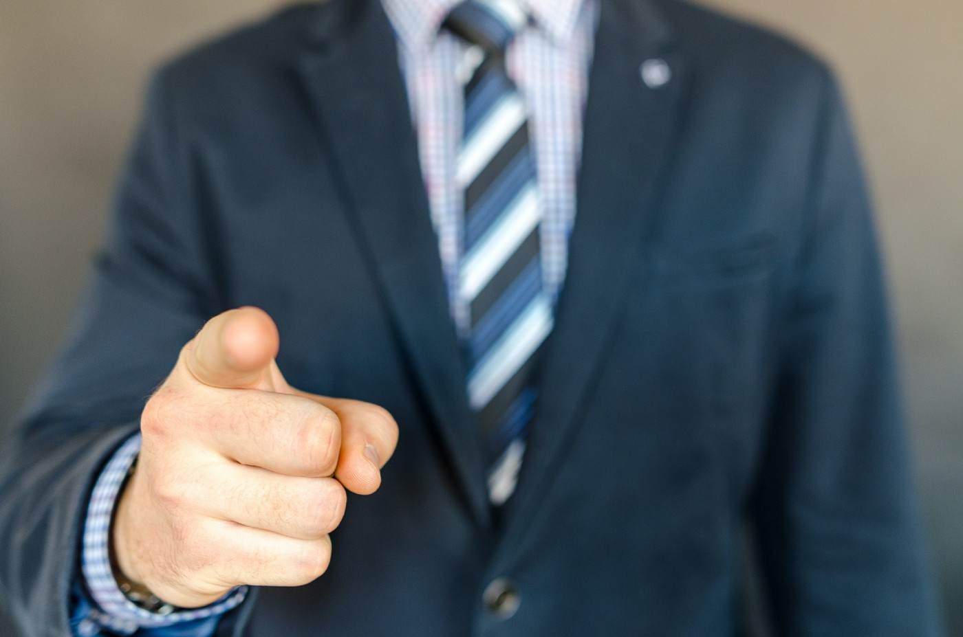 A person with coat and tie pointing his index finger towards the camera
