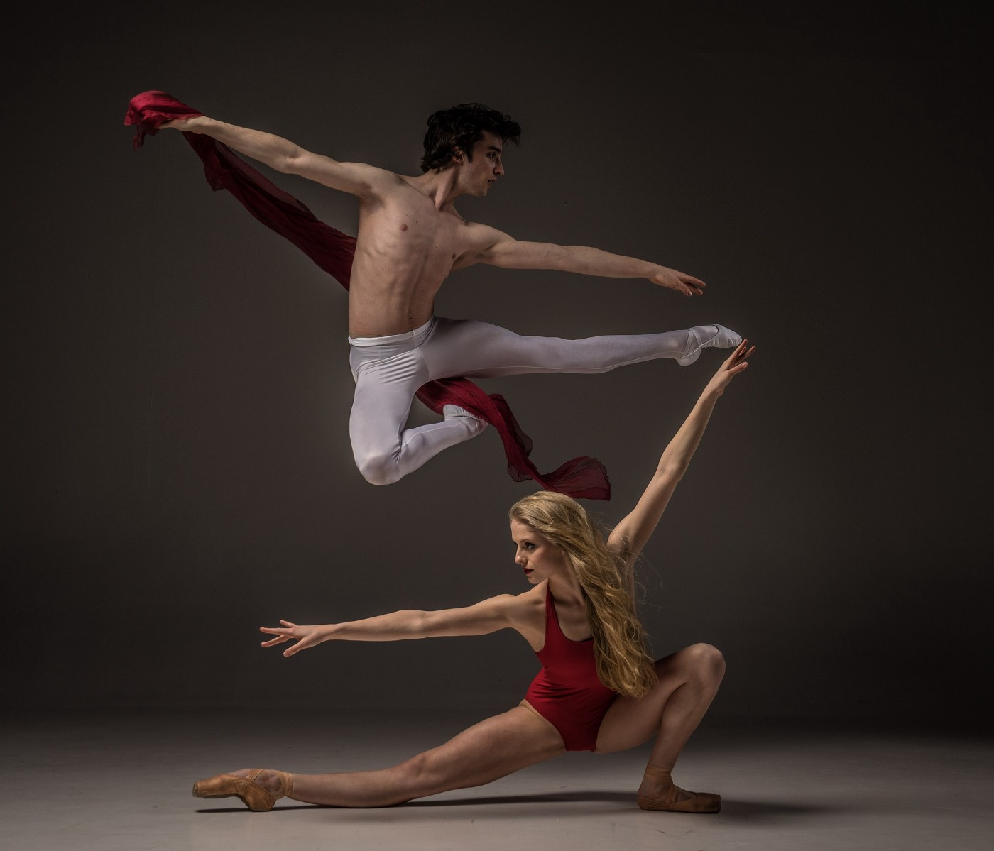 A male ballet dancer leaping over a female dancer with her arms stretched out.