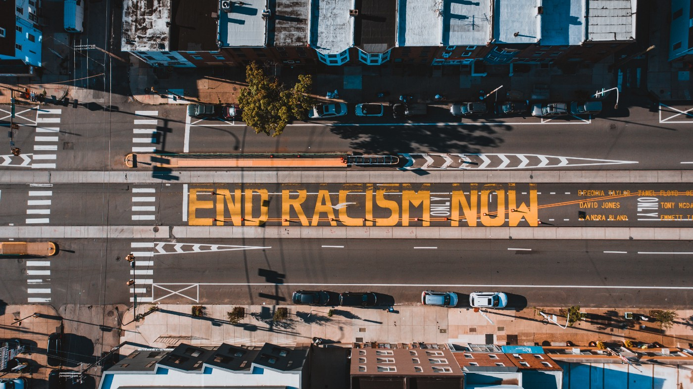 "This shows an aerial view of the street that has ""end racism now"" painted on it in yellow."