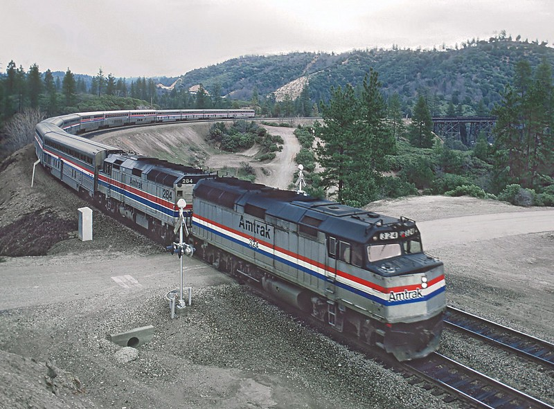 An Amtrak train traversing a forested, hilly area
