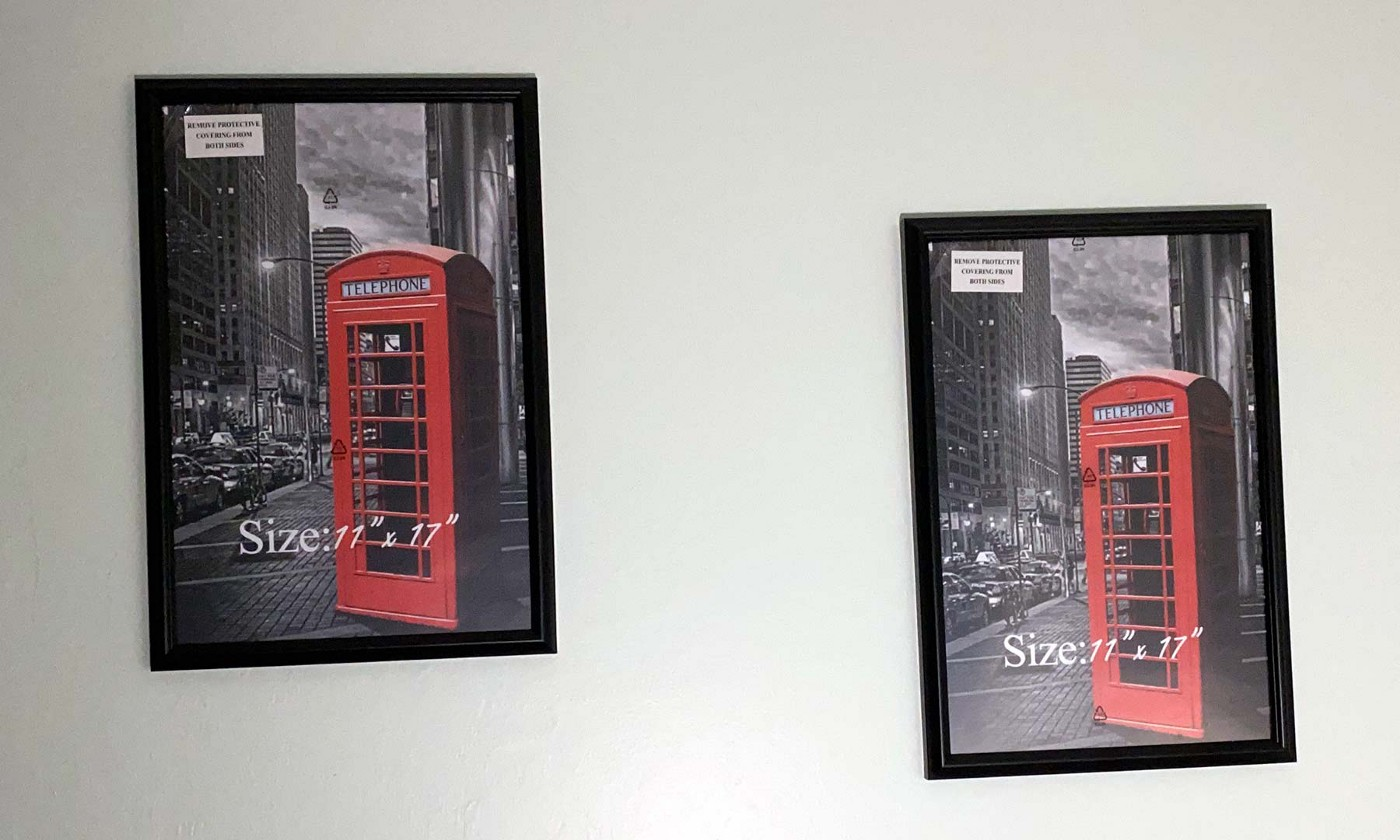 Two poster frames hang on a wall, display the manufacturer's supplied image.