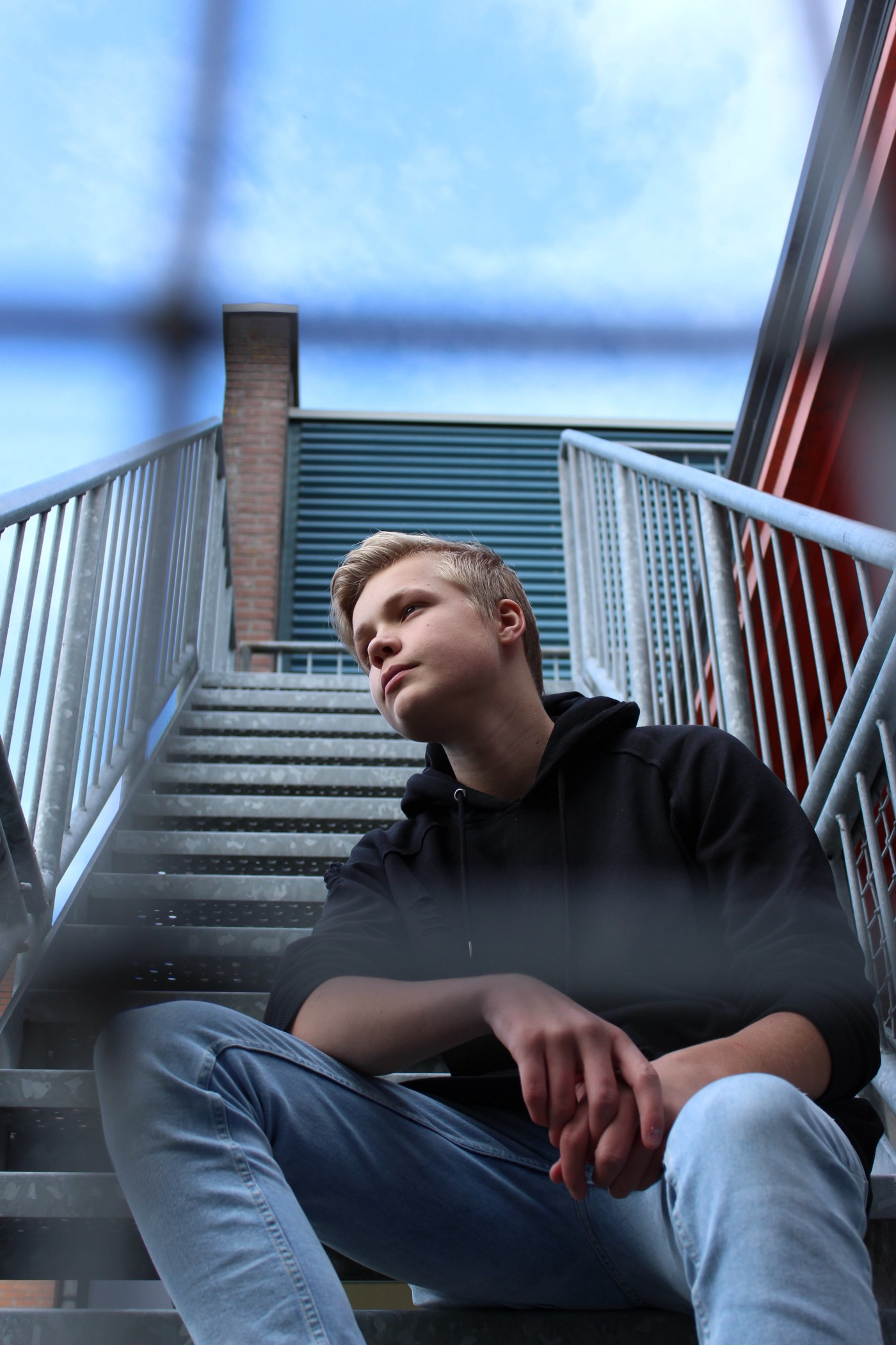 Young blonde boy sitting on concrete stairs.