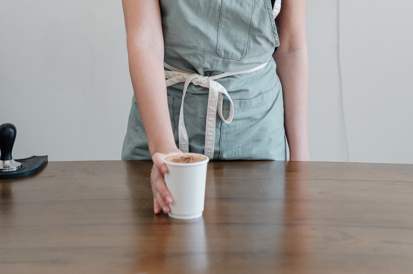 A woman serving a cup of coffee across a counter