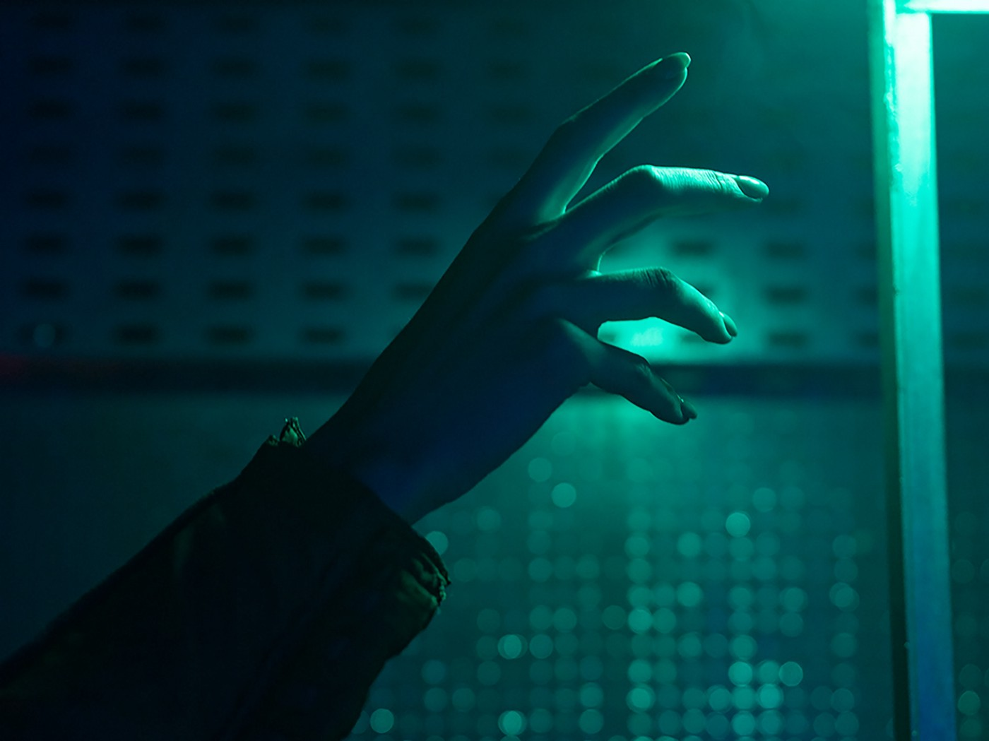 Hand reaches towards a green tinted light in an industrial, high tech background