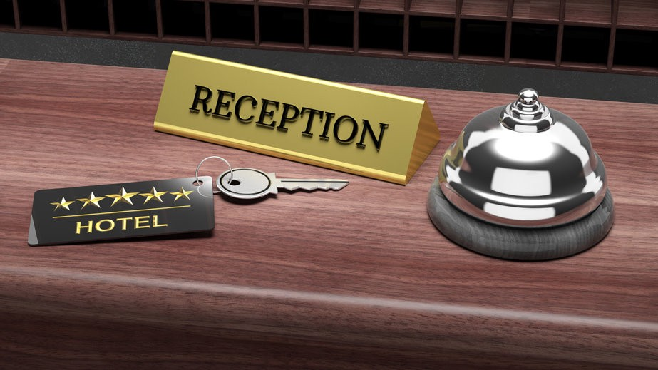 A hotel key, reception desk sign and bell to ring for service