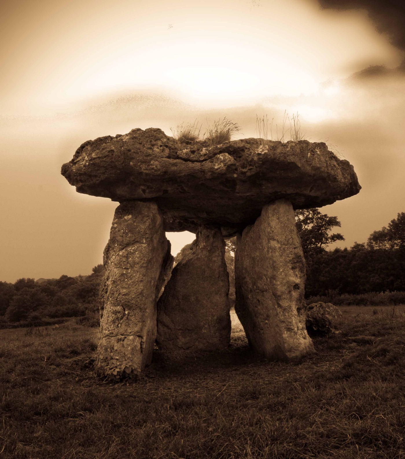 A photograph of St Lythan's Burial Chamber in sepia tones.