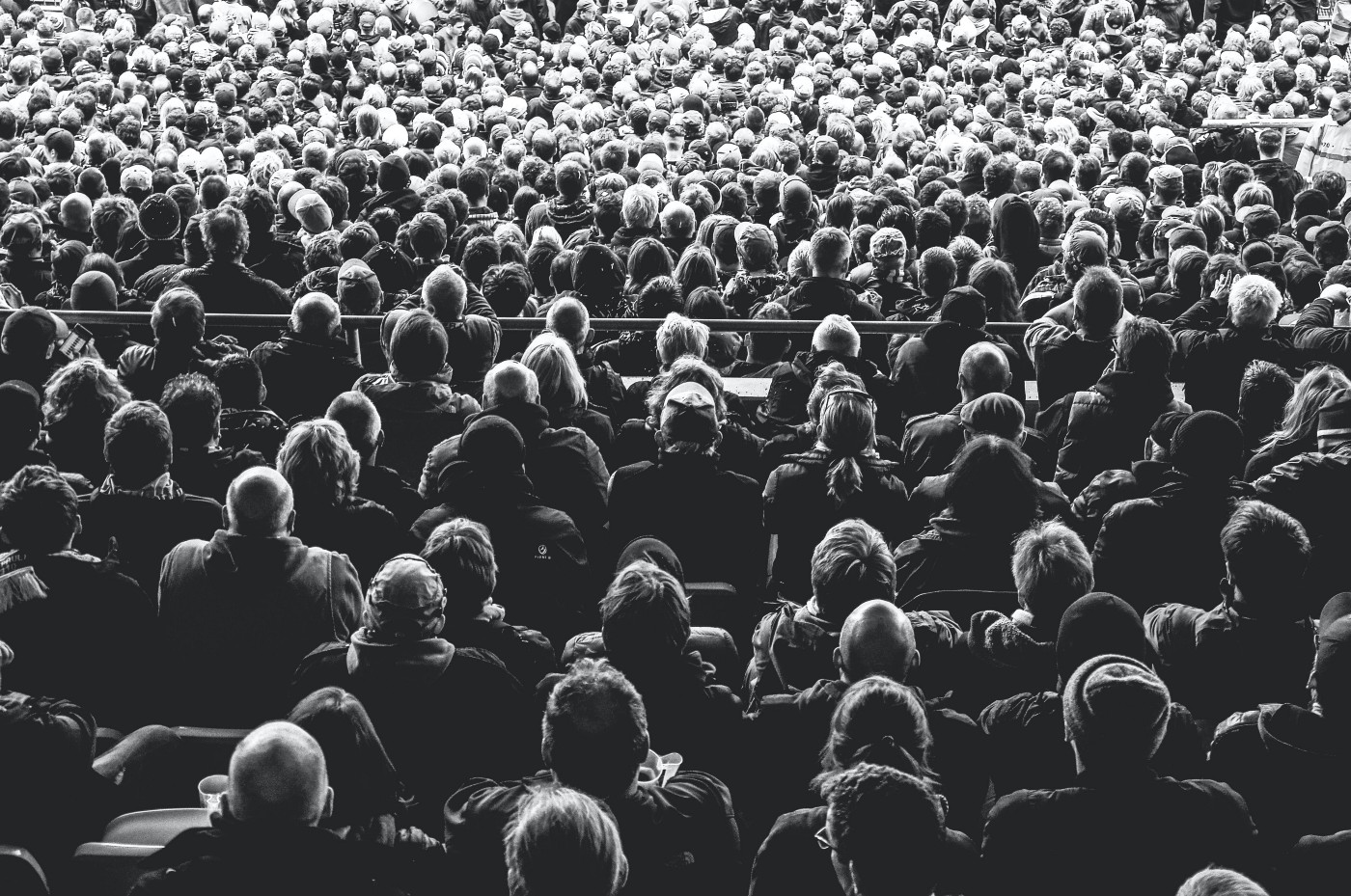An audience facing away from the viewer, seen in black-and-white.
