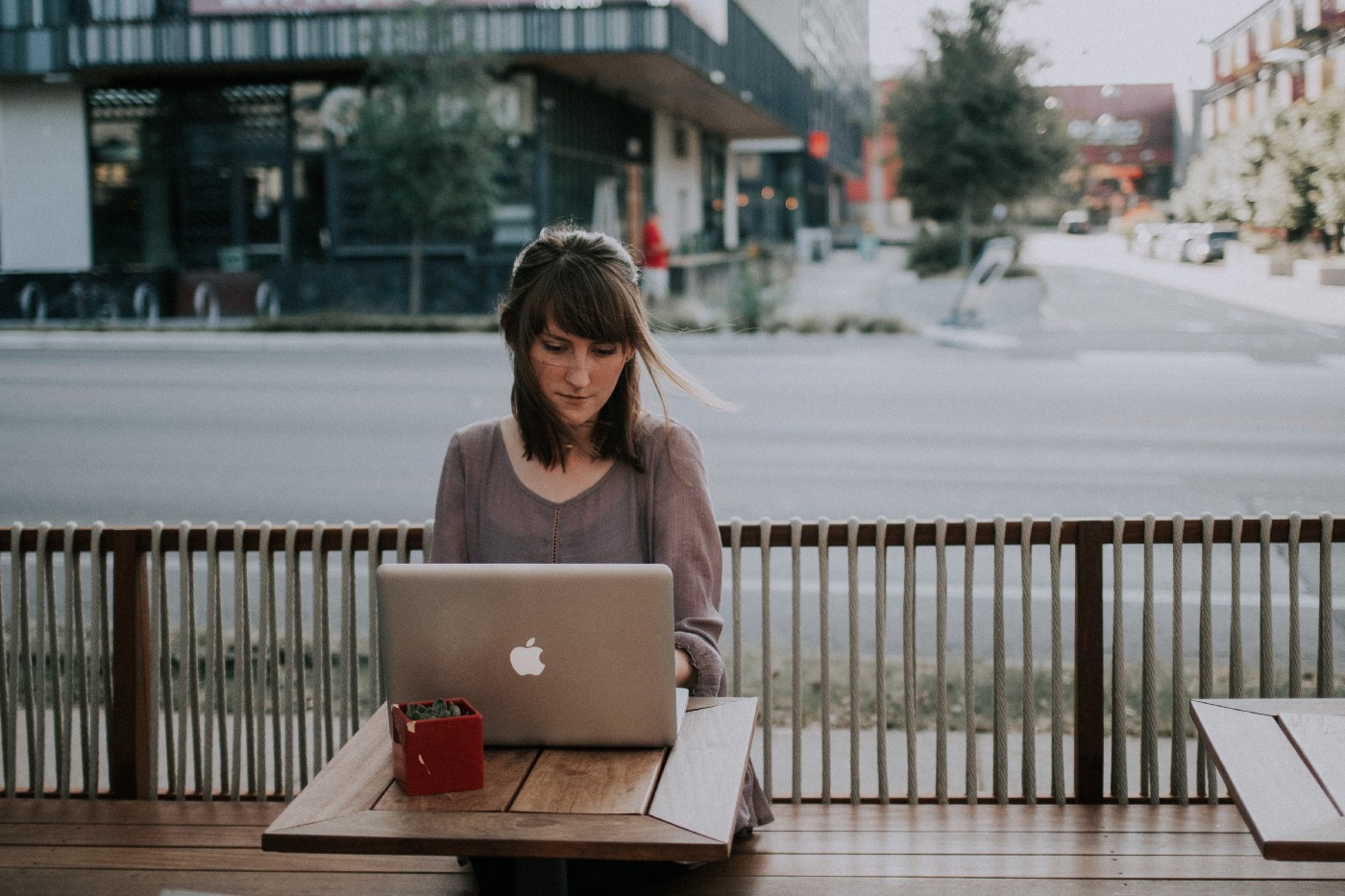 A woman sits outside and works on her laptop.