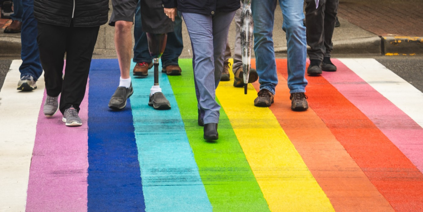 A group of people walking on a road that is painted rainbow colors