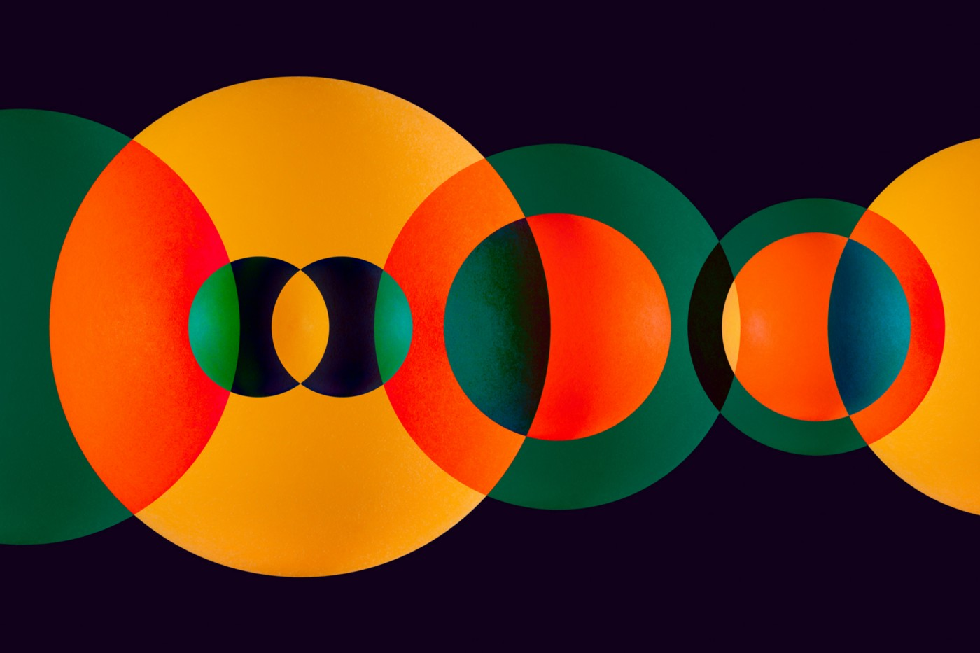 Green and orange circle spheres overlapping on solid dark background.