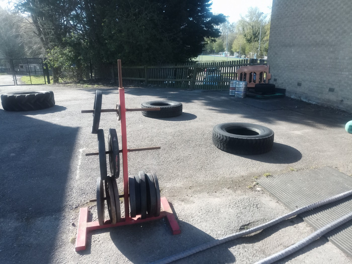 a rack with plates of metal barbell weights. In the background large heavy tyres