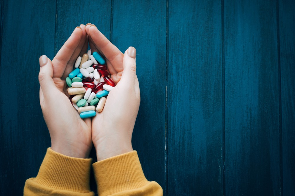Two hands holding a large amount of various pills.