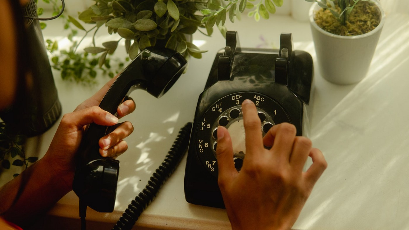 A person dialing on a rotary phone