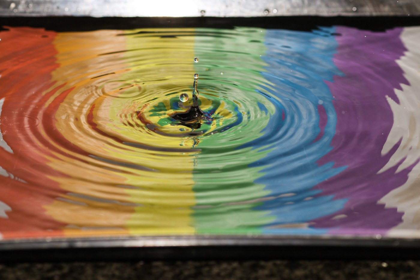 A pool of water with rainbow coloring and ripples in the water