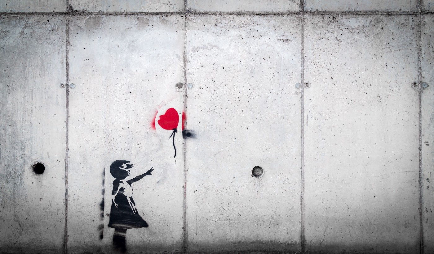Street art showing a child letting go of a heart-shaped balloon