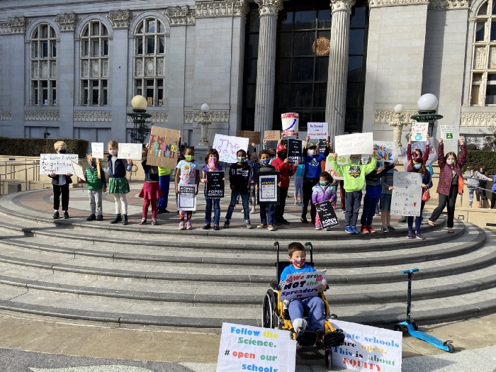Protesters with signs standing on rounded steps before a City building. One protester, a wheelchair user, sits in front.
