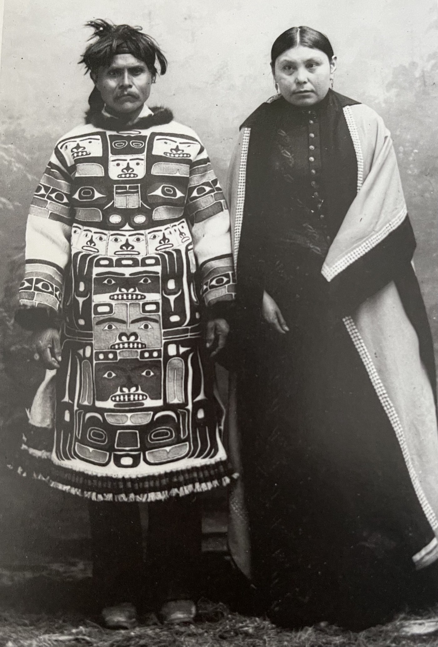 Husband in traditional attire woven geometric patterns of animals and human faces and hands. Wife in colonial black buttoned dress and cloak with shell trim.