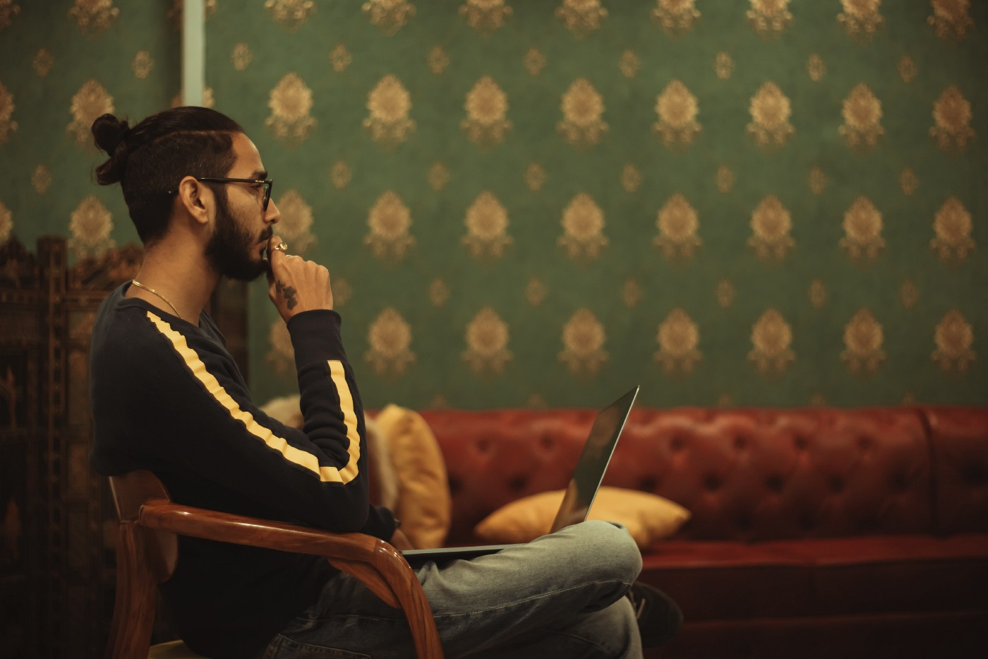 A man sitting on a chair working on his laptop