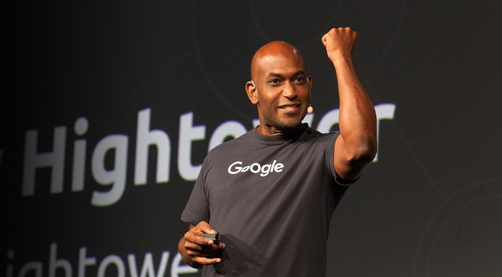 Image description: Kelsey Hightower presenting at HashiConf, triumphantly raising his fist in emphasis of something, likely Kubernetes related.