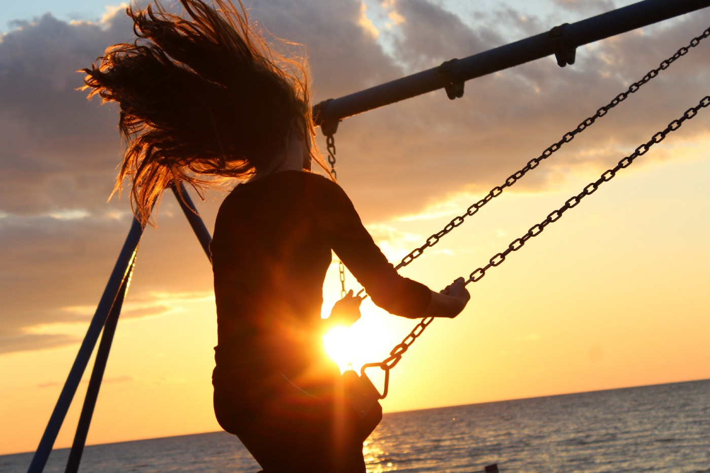 Woman in a swing, hair flying behind her, probably on a beach because she seems to be swinging over the sun setting on the ocean
