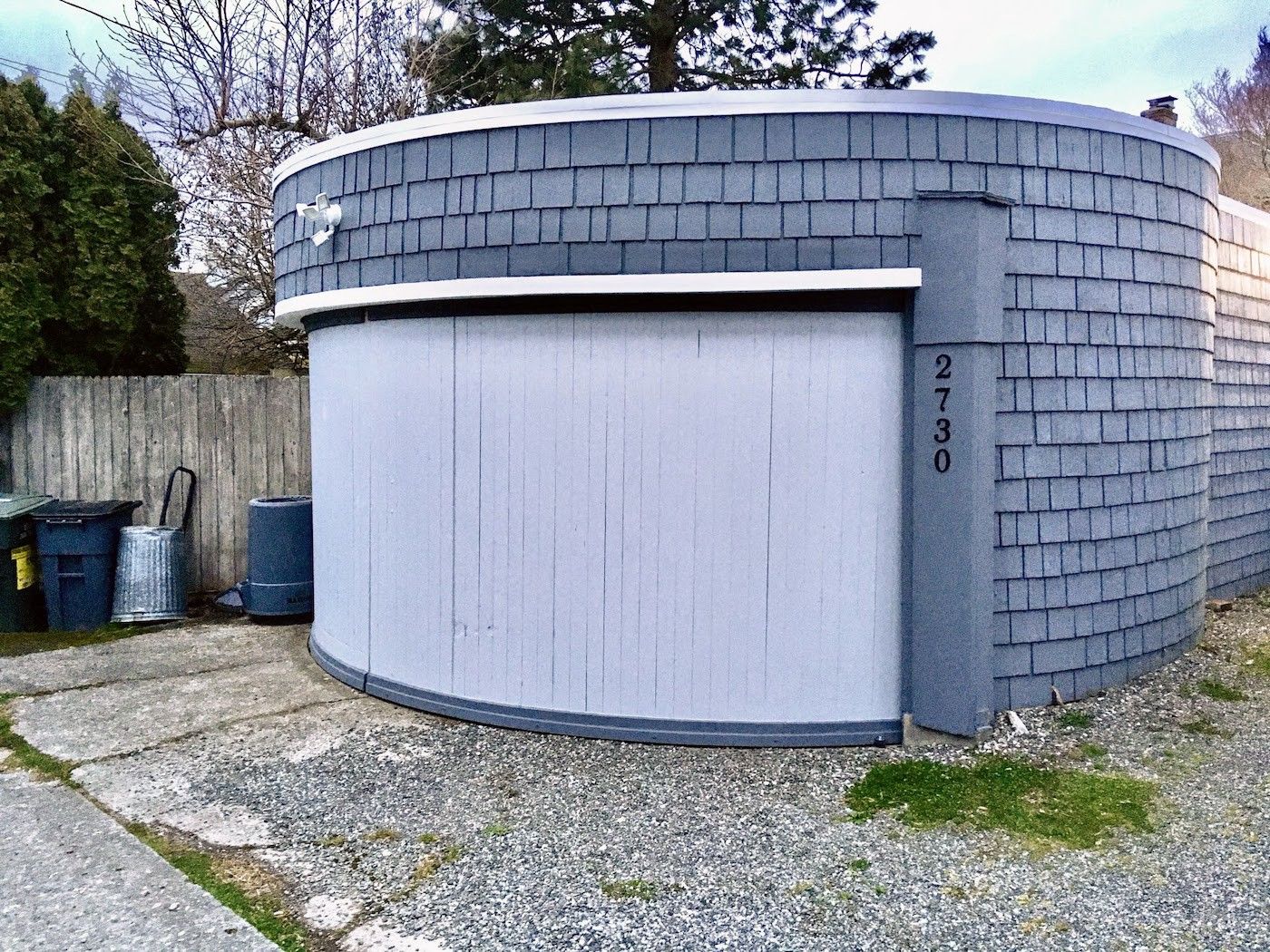 A round fronted, stand-alone garage with a curved rolling door and shingled sides facing an alley.