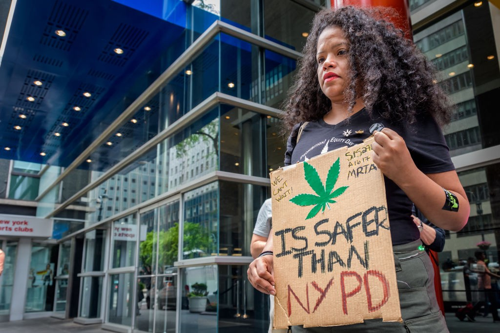 """Woman holds a sign during a rally that says """"[Marijuana leaf] is safer than NYPD."""""""