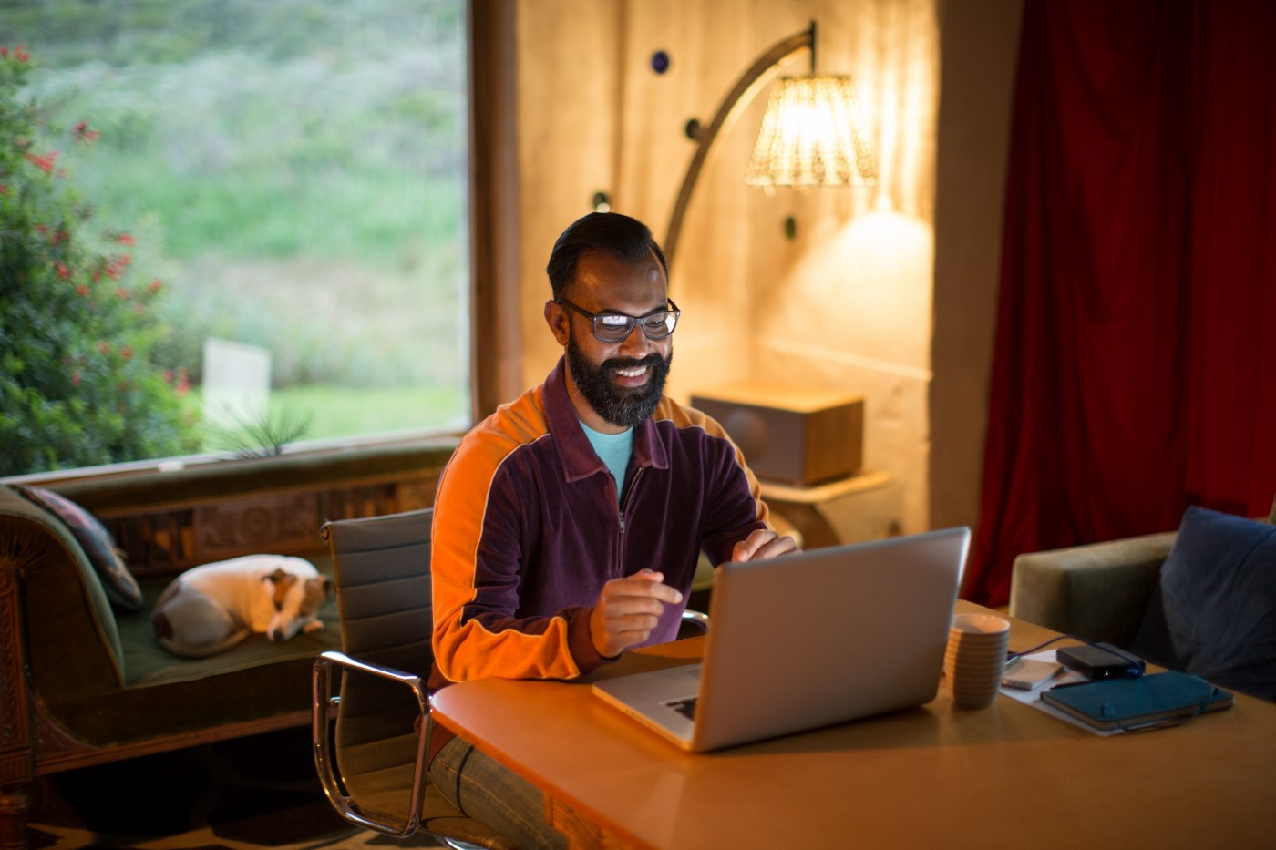 Mixed race man working from home on his computer, smiling