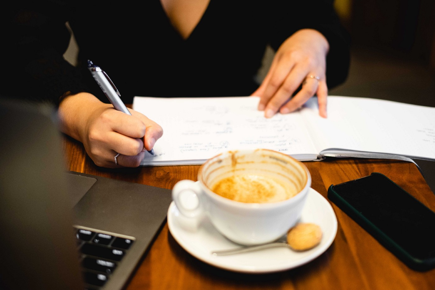 Woman sitting at a desk with a coffee, writing with a notebook and computer next to her.