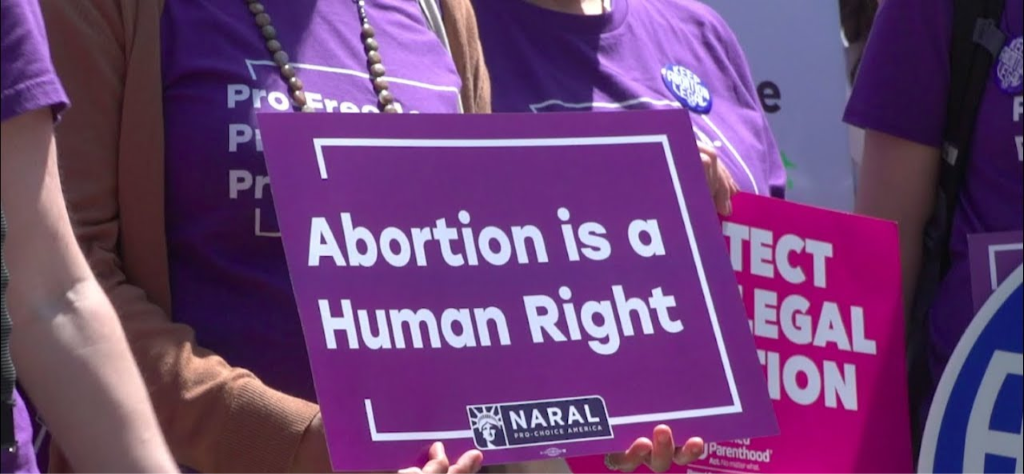 "Advocate holding a sign that says ""Abortion is a Human Right"""